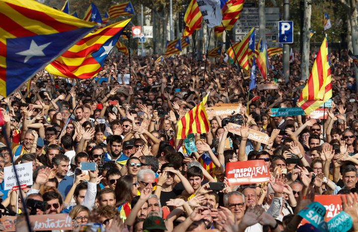 People react as they watch on giant screens a plenary session outside the Catalan regional parliament in Barcelona, Spain, Oc