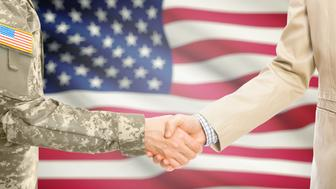 American soldier in uniform and civil man in suit shaking hands with national flag on background - United States