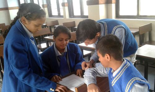 Student participants at a school in New Delhi, India, prepare to read the UHDR in Hindi (Source: UHRI)