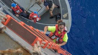 Tasha Fuiaba an American mariner who had been sailing for five months on a damaged sailboat climbs the accommodation ladder to board the amphibious dock landing ship USS Ashland