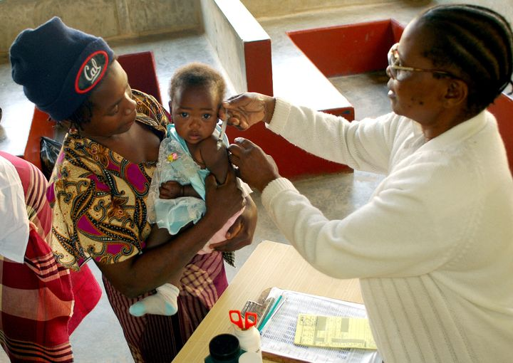 Health workers vaccinates child against measles at provincial hospital in Xai Xai, north of Mozambique's capital Maputo, August 11, 2005.