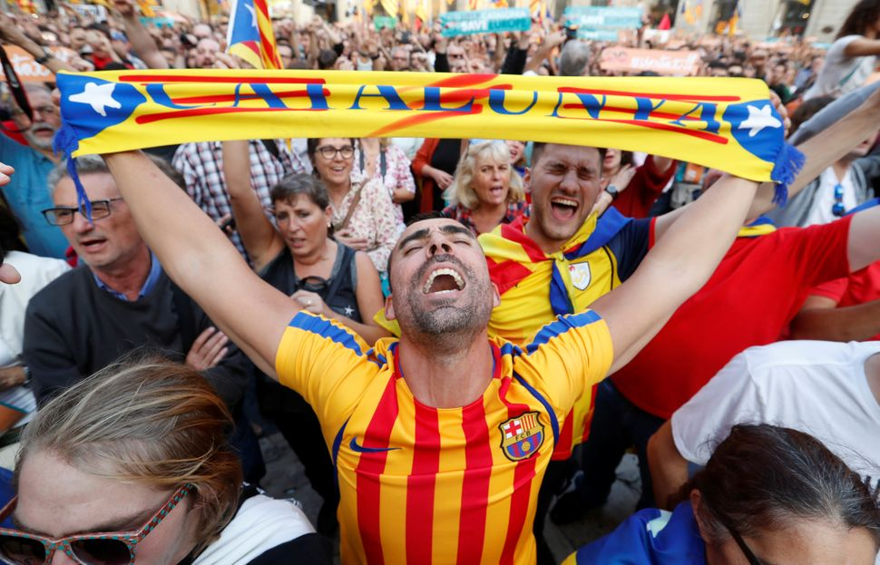People react at Sant Jaume Square in Barcelona after the Catalan regional parliament declares independence from Spain.
