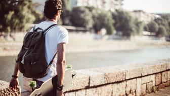 Handsome Man holding longboard is taking a walk by the river, on a sunny summer day outdoors.