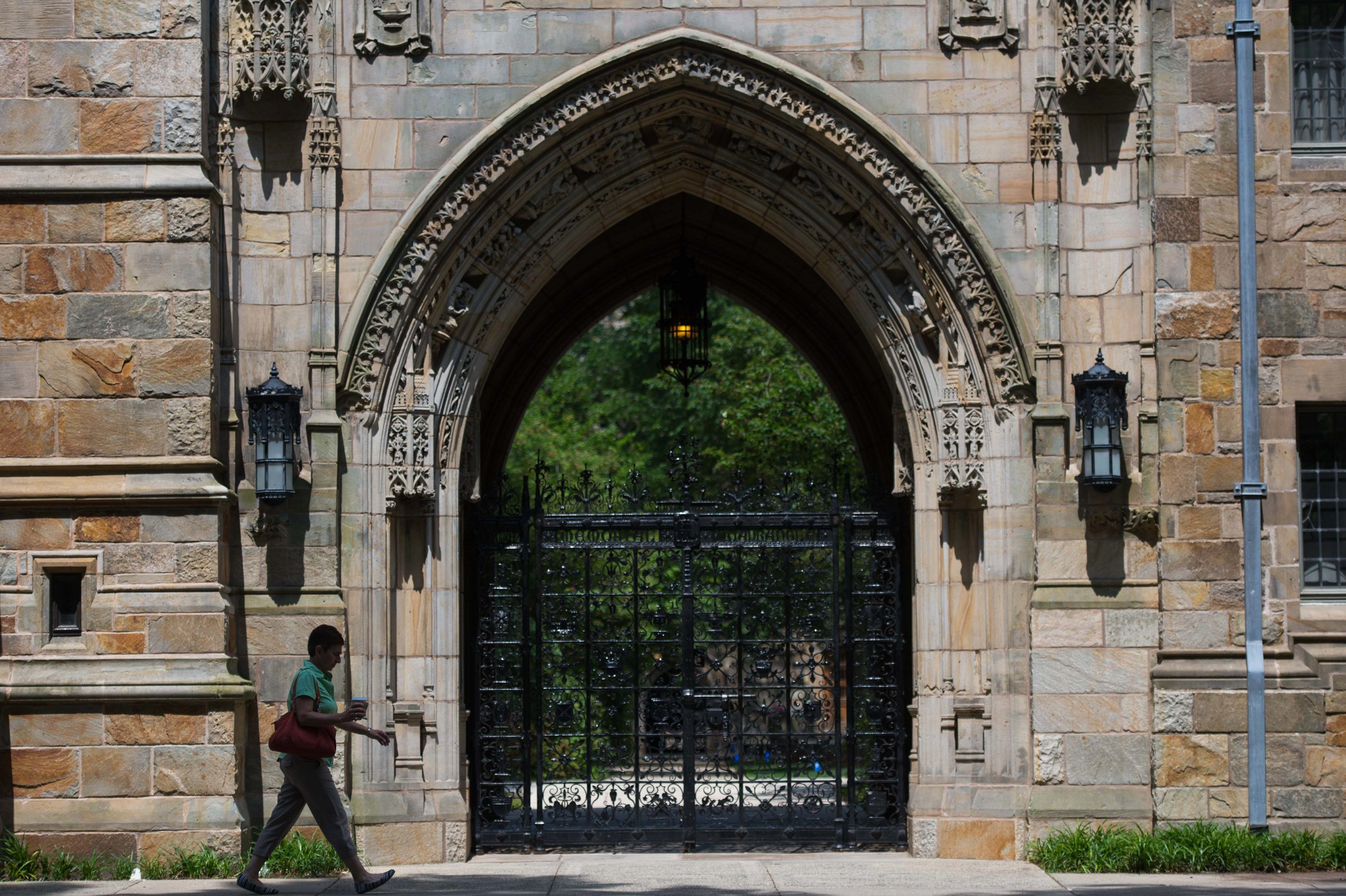 A pedestrian walks past Harkness Gate on the Yale University campus in New Haven, Connecticut, U.S., on Friday, June 12, 2015. Yale University is an educational institute that offers undergraduate degree programs in art, law, engineering, medicine, and nursing as well as graduate level programs. Photographer: Craig Warga/Bloomberg via Getty Images