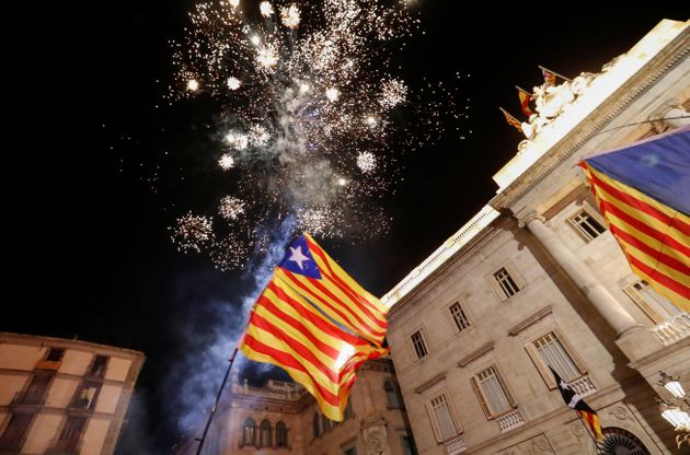 Catalan separatist flags are held up as fireworks go off in Sant Jaume Square in front of the Catalan...