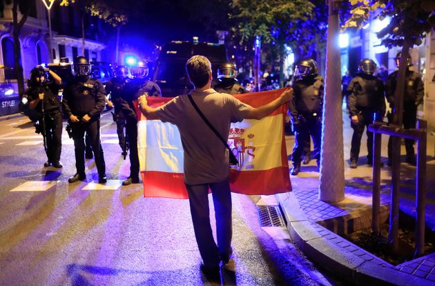 A pro unity demonstrator displays a Spanish flag to Catalan Regional Police