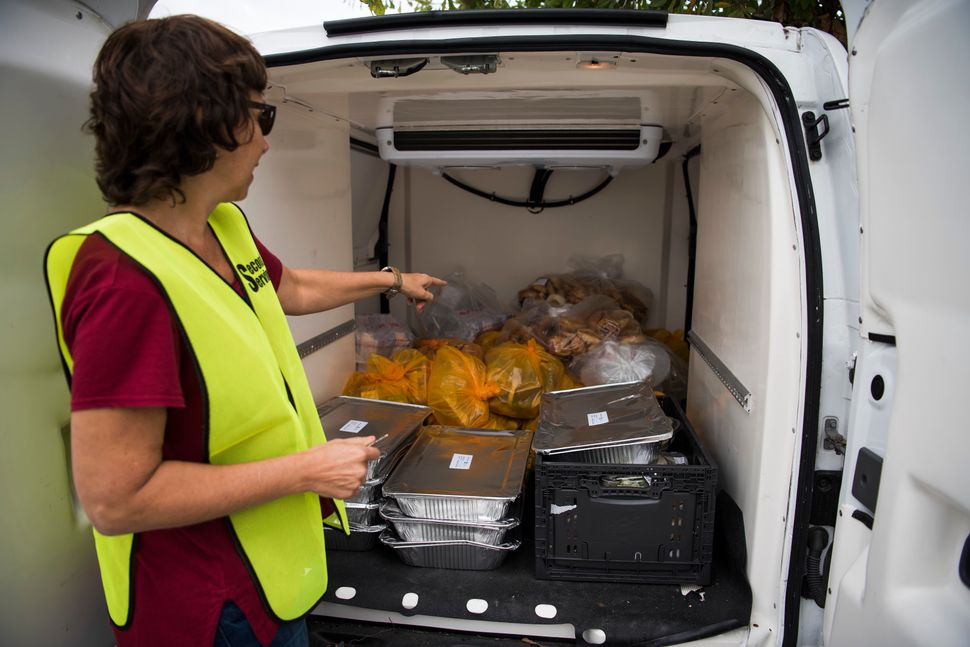 """Annette Liftman shows leftover food that had been picked up by the organization """"Second Servings."""""""