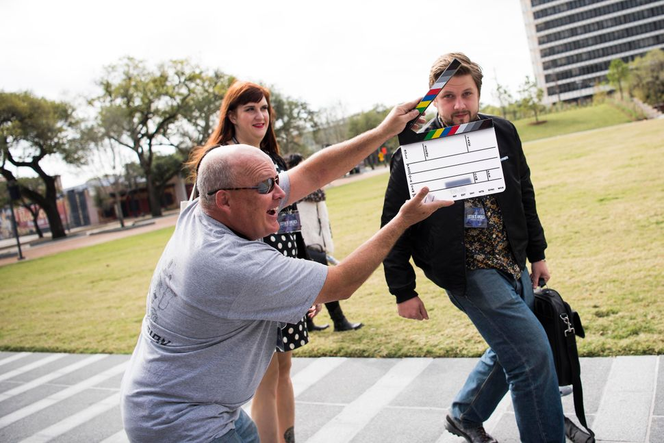 Brad Cowgill plays around by holding a film slate in front of Will Tookeand Emily McCombs.