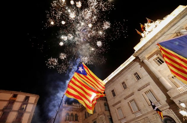 Catalan separatist flags are held up as fireworks go