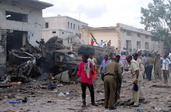 Somali security officers assess the damage at the scene of a suicide car bomb explosion, at the gate of Naso Hablod Two Hotel