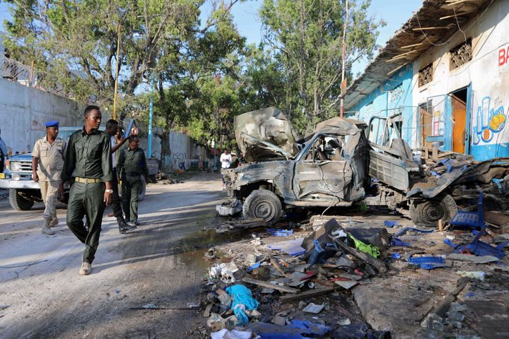 Somali security officers assess the scene of a suicide car bomb explosion, at the gate of Naso Hablod Two Hotel in Hamarweyne