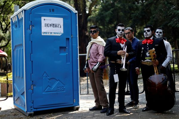 Mariachis wait to enter a bathroom before taking part in a procession to commemorate Day of the Dead in Mexico City on Saturd