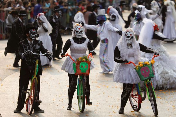 People wearing skull costumes are seen in Mexico City on Saturday.