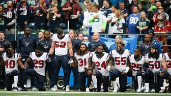 SEATTLE, WA - OCTOBER 29:  Members of the Houston Texans stand and kneel before the game against the Seattle Seahawks at CenturyLink Field on October 29, 2017 in Seattle, Washington. During a meeting of NFL owners earlier in October, Houston Texans owner Bob McNair said 'we can't have the inmates running the prison', referring to player demonstrations during the national anthem. (Photo by Otto Greule Jr/Getty Images)