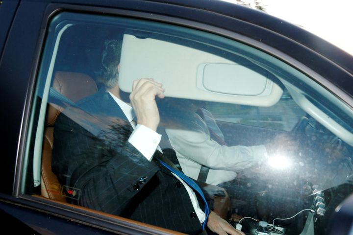 Paul Manafort hides behind his car visor as he leaves his home in Alexandria, Virginia, on Monday.
