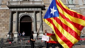 A man holding a Catalan separatist flag (L) looks at men holding a Spanish flag outside the Generalitat Palace, the Catalan regional government headquarters in Barcelona, Spain, October 30, 2017. REUTERS/Juan Medina