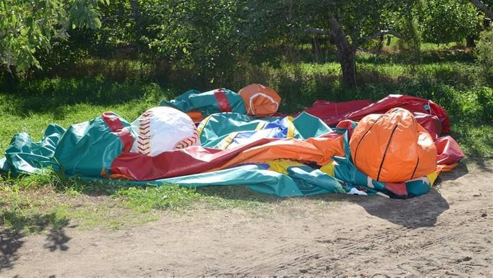 A deflated bounce house sits where it fell after soaring into the sky with two children inside at a Halloween festival in Nas
