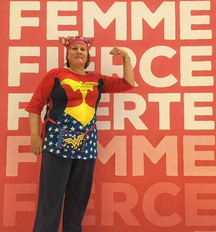 "Karen Dunnam, 60, posed in front of a poster at the Women's Convention wearing her fall ""pussy hat."""
