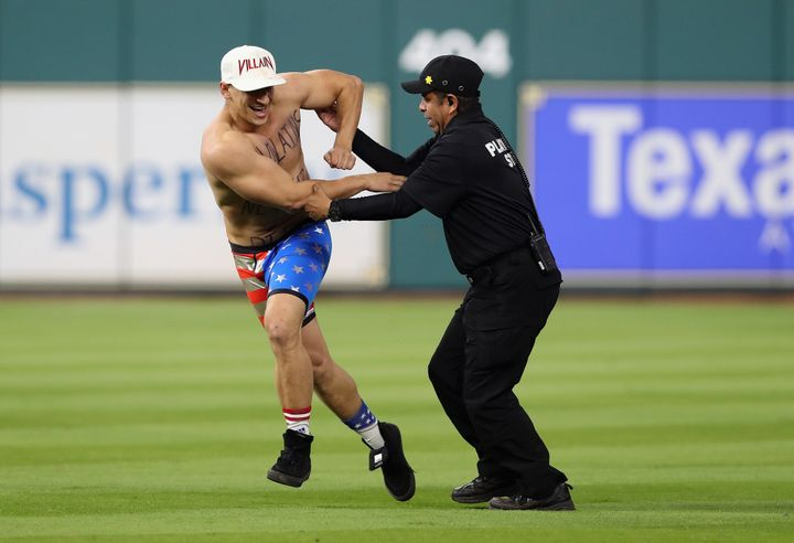 Security apprehends a man during Game 5 of the 2017 World Series between the Houston Astros and the Los Angeles Dodgers