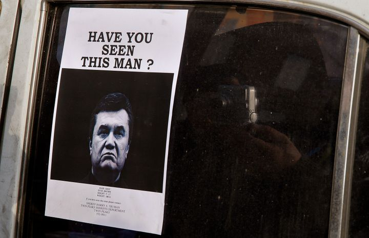 A man takes photos of a wanted notice of fugitive Ukrainian President Victor Yanukovich.