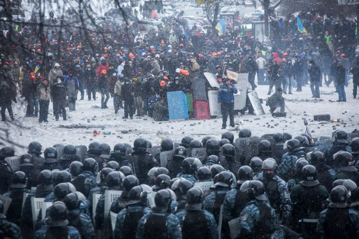 Riot police and Interior Ministry members stand in formation in front of pro-European protesters during clashes in Kiev on Ja