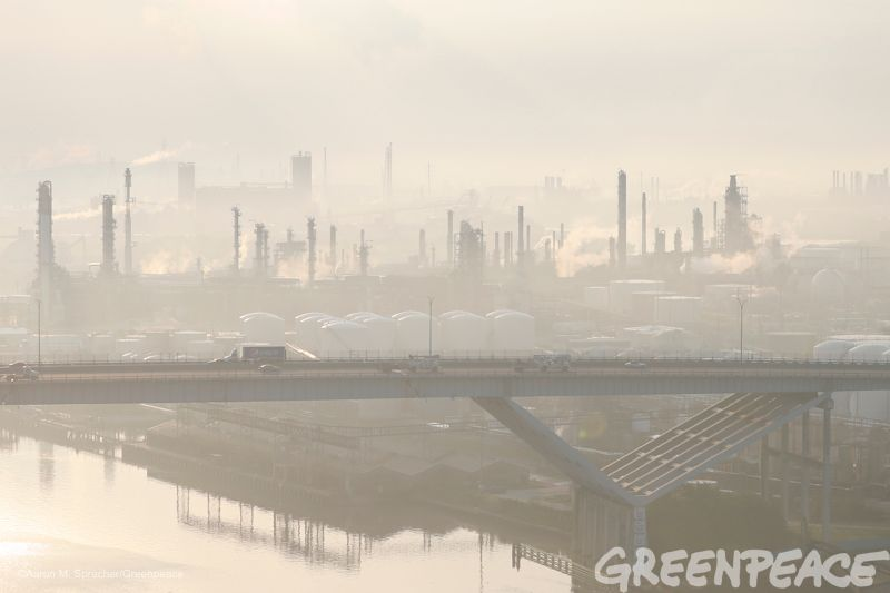 Vehicles make their way across a bridge in haze from the oil refining industrial complex behind them in Manchester, Texas, mo