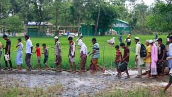 Rohingya Muslims, who crossed over from Myanmar into Bangladesh, walks through muddy field after collecting aid from a distribution centre near Balukhali refugee camp, Bangladesh, October 2, 2017. The United Nations' humanitarian office said Thursday that the number of Rohingya Muslims fleeing to Bangladesh since Aug. 25 has topped 500,000.