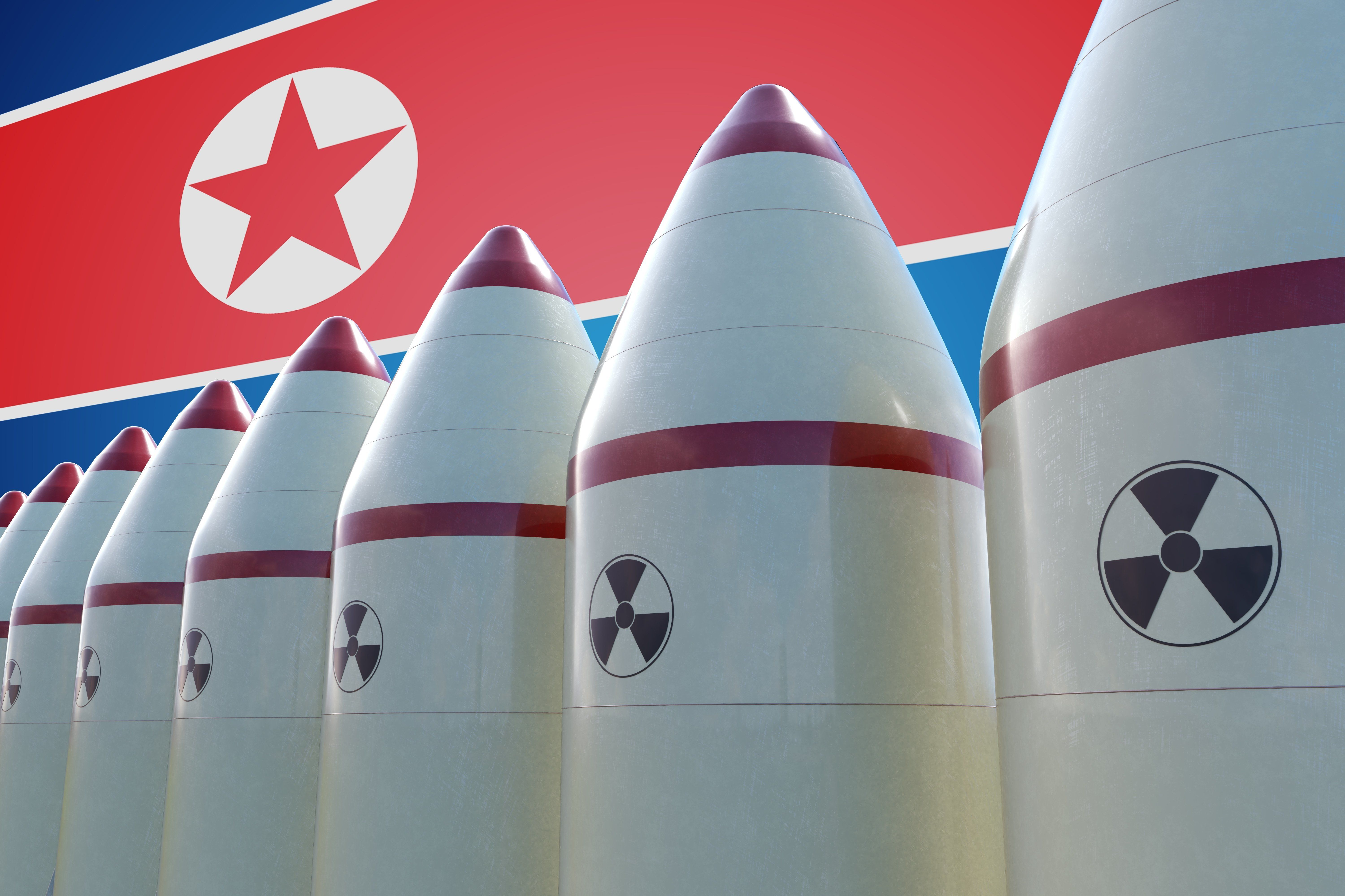 Nuclear missiles and North Korea flag in background. 3D rendered illustration.