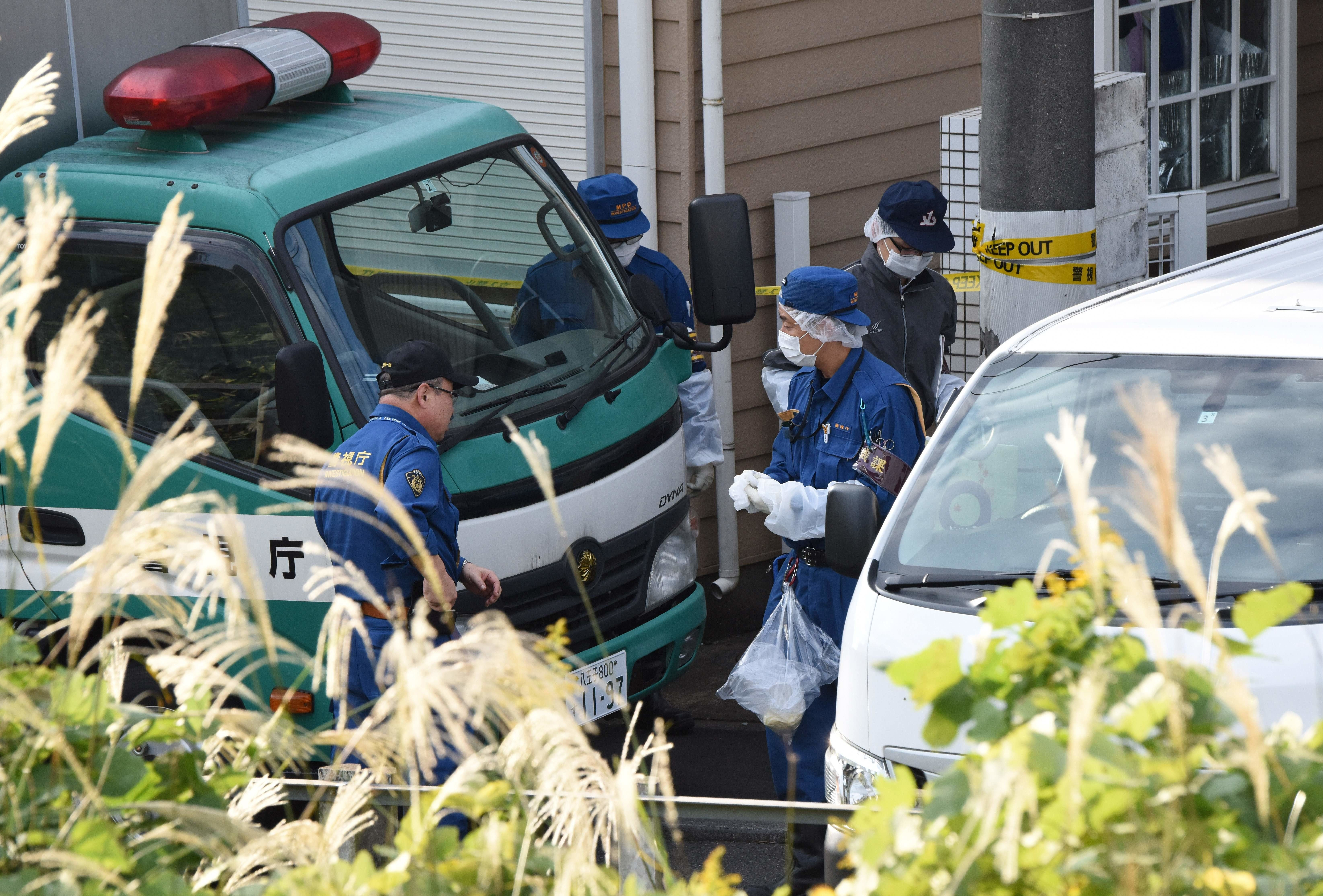 Japanese police officers gather in front of an apartment in Zama, Kanagawa prefecture, where nine dismembered bodies were fou