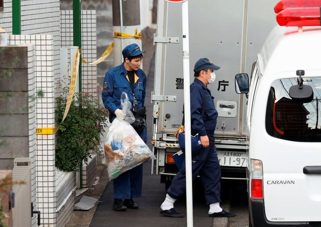 A police officer carries out a plastic bag from an apartment building after the discovery of nine