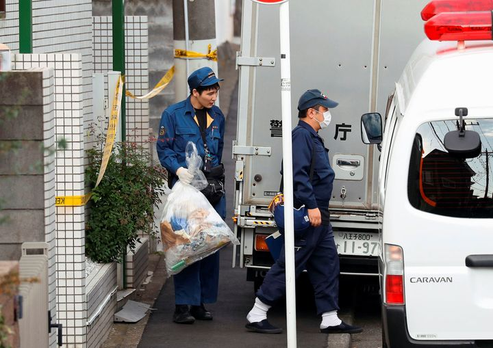 A police officer carries out a plastic bag from an apartment building after the discovery of nine bodies