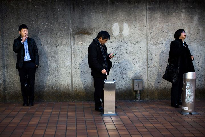Men smoke cigarettes at a designated outdoor smoking area in the Naka-Meguro neighborhood of Tokyo. A local company is offeri