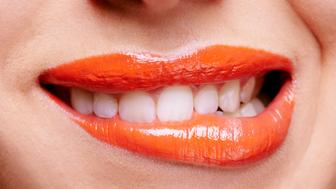 Cropped shot of a woman biting her orange colored lipshttp://195.154.178.81/DATA/i_collage/pi/shoots/783619.jpg