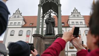 People take pictures of a statue of German Church reformer Martin Luther holding a book including his translation into German of the New Testament of the Bible at the main square in front of the city hall in Wittenberg, eastern Germany, where celebrations take place on the occasion of the 500th anniversary of the Reformation on October 31, 2017. It is presumed that October 31, 1517 is the date that German theologian Martin Luther published his groundbreaking '95 Theses' of criticism of the Catholic Church, which marks the start of the process that led Protestants to break away from the Roman Catholic Church, a revolution for the Christian religion. The Reformation caused major upheaval in Europe, leading to wars, persecutions and exoduses, including the departure of the Pilgrims for what was later to become America. / AFP PHOTO / DPA / Hendrik Schmidt / Germany OUT        (Photo credit should read HENDRIK SCHMIDT/AFP/Getty Images)