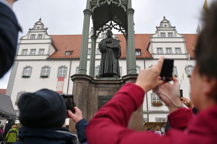 People take pictures of a statue of German Church reformer Martin Luther holding a book including his translation into German