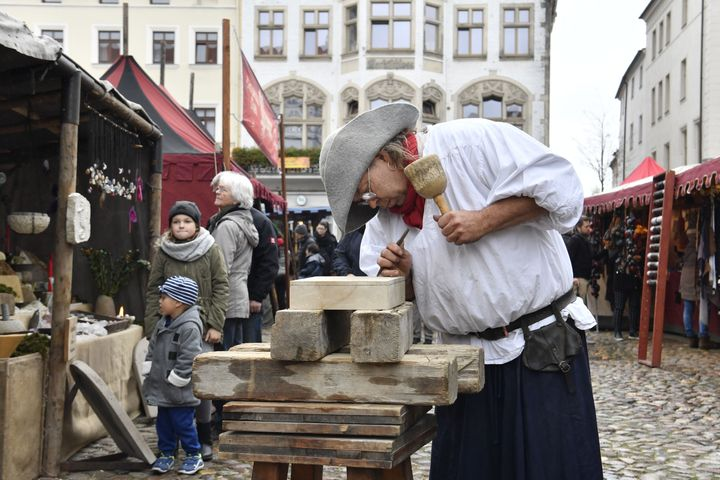 A traditional wood cutter engraves wood in the main square in Wittenberg, eastern Germany, where celebrations take place on t