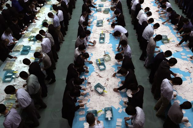 Electoral officials count ballots for the general election at the Himeji City Office in Himeji, Hyogo...