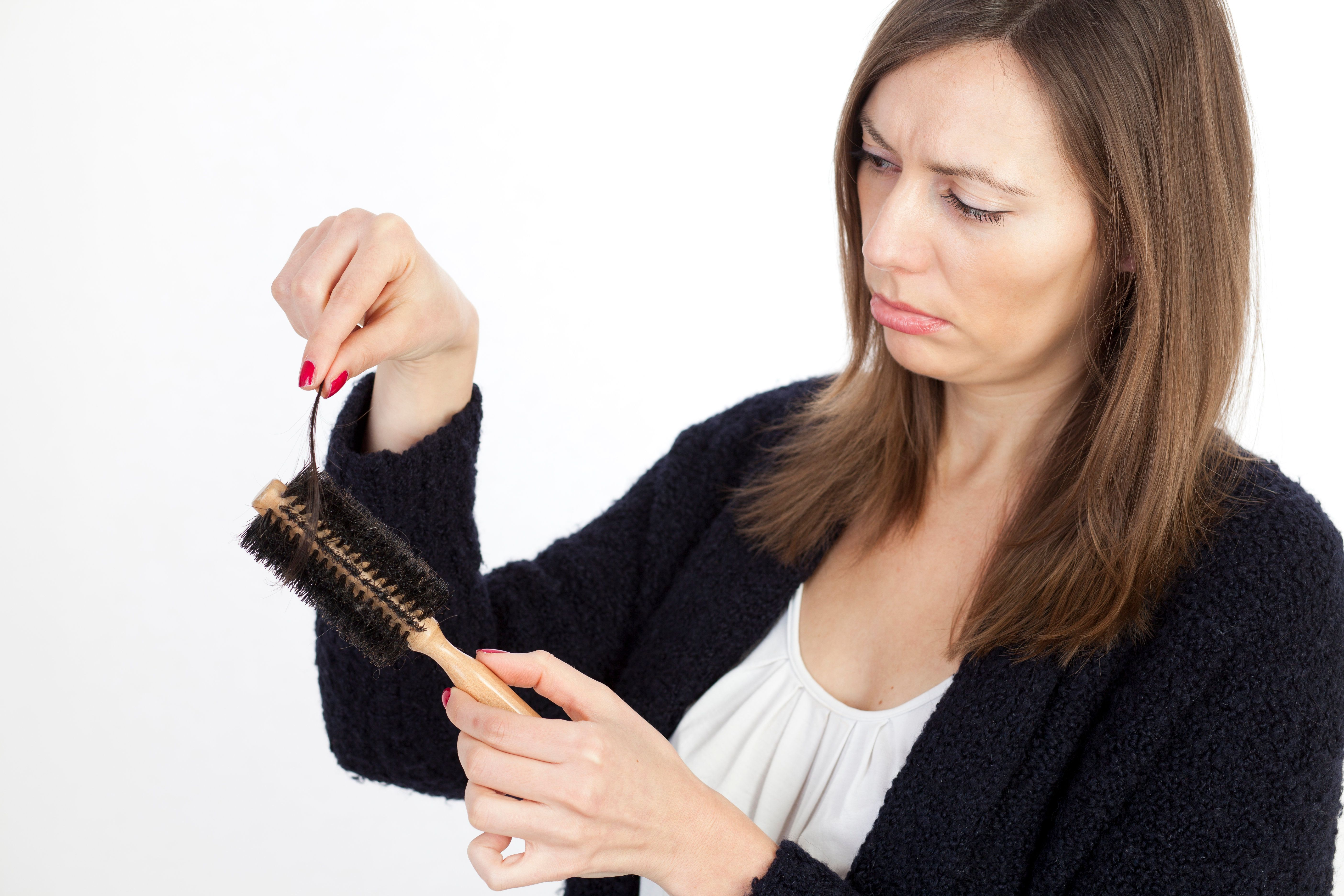Caucasian woman cleaning her brush from her hair