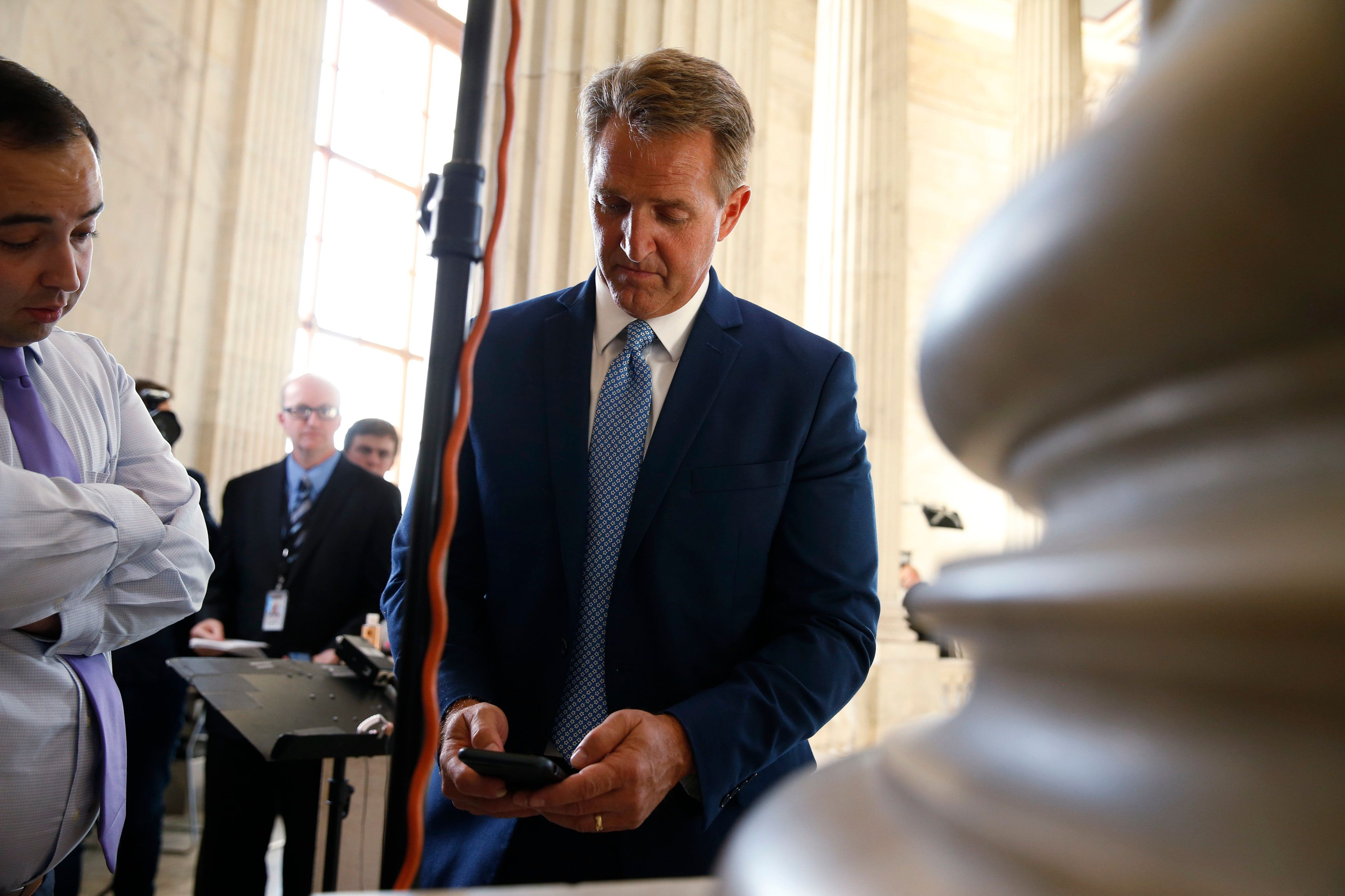 U.S. Senator Jeff Flake (R-AZ) pauses to check his phone after announcing he will not run for reelection on Capitol Hill in Washington, U.S., October 24, 2017. REUTERS/Joshua Roberts