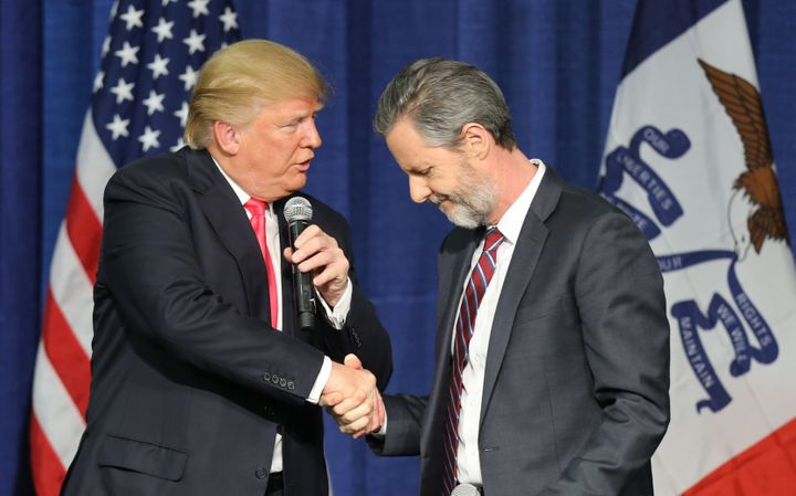 Then-presidential candidate Donald Trump (L) shakes hands with Jerry Falwell Jr. at a campaign rally in Council Bluffs, Iowa,