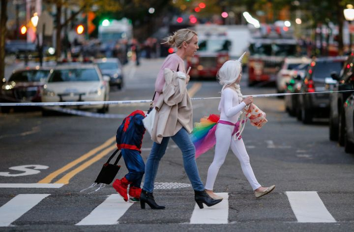 Kids in Halloween costumes cross the street near the scene where eight people were killed earlier in the day in a suspected t