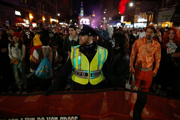 NYPD officers stand guard during the Halloween parade hours after a man driving a rental truck struck...