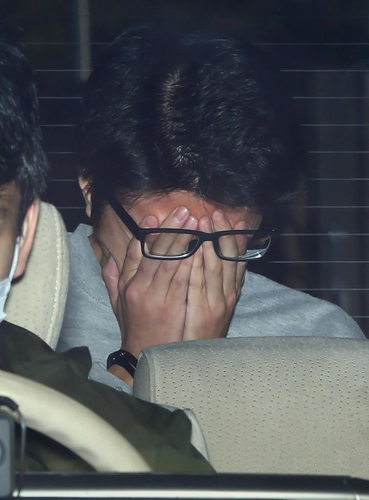 Suspect Takahiro Shiraishi covers his face with his hands as he is transported to the prosecutor's office from a police station in Tokyo on 1 November