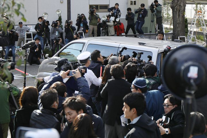 Photographers surround a police van transporting the suspect from a police station to the prosecutor's office in Tokyo