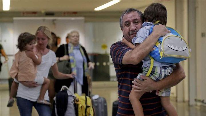 Cori Rojas, left, carries her daughter through JFK Airport after a flight from San Juan, Puerto Rico. Rojas, a school teacher