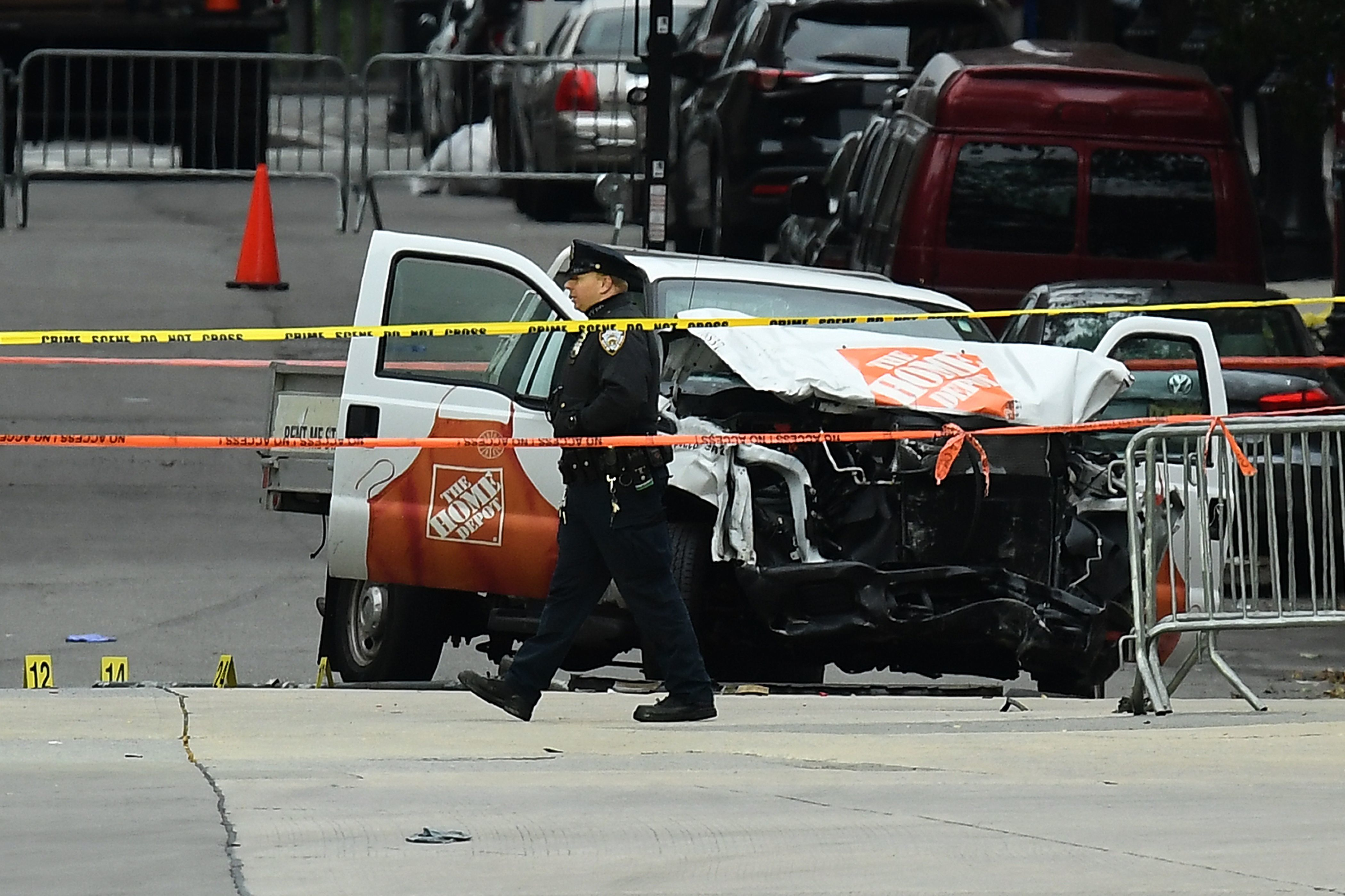 A police officer walks past the wreckage of a Home Depot pickup truck, a day after it was used in an terror attack, in New York on November 1, 2017. The pickup truck driver who plowed down a New York cycle path, killing eight people, in the city's worst attack since September 11, was associated with the Islamic State group but 'radicalized domestically,' the state's governor said Wednesday. The driver, identified as Uzbek national named Sayfullo Saipov was shot by police in the stomach at the end of the rampage, but he was expected to survive. / AFP PHOTO / Jewel SAMAD        (Photo credit should read JEWEL SAMAD/AFP/Getty Images)