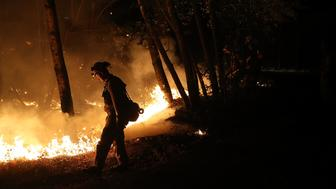 CALISTOGA, CA - OCTOBER 12:  CalFire firefighter Brandon Tolp uses a drip torch during a firing operation while battling the Tubbs Fire on October 12, 2017 near Calistoga, California. At least thirty one people have died in wildfires that have burned tens of thousands of acres and destroyed over 3,500 homes and businesses in several Northern California counties.  (Photo by Justin Sullivan/Getty Images)