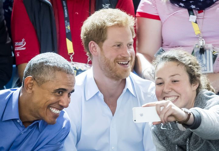 A woman takes a selfie with Obama and Prince Harry at the 2017 Invictus Games.