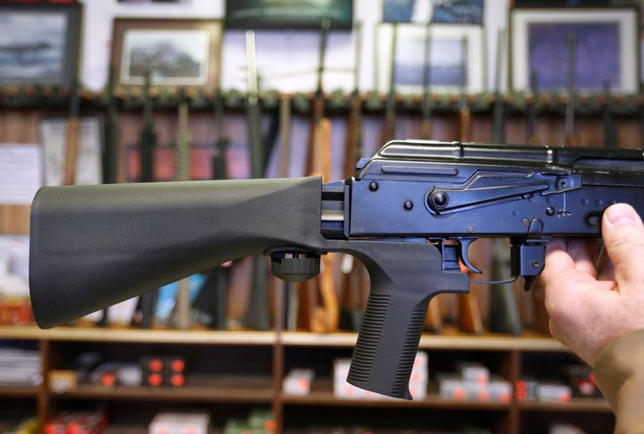 A bump stock device, which fits on a semi-automatic rifle to increase the firing speed, is installed on an AK-47 at a gun sto