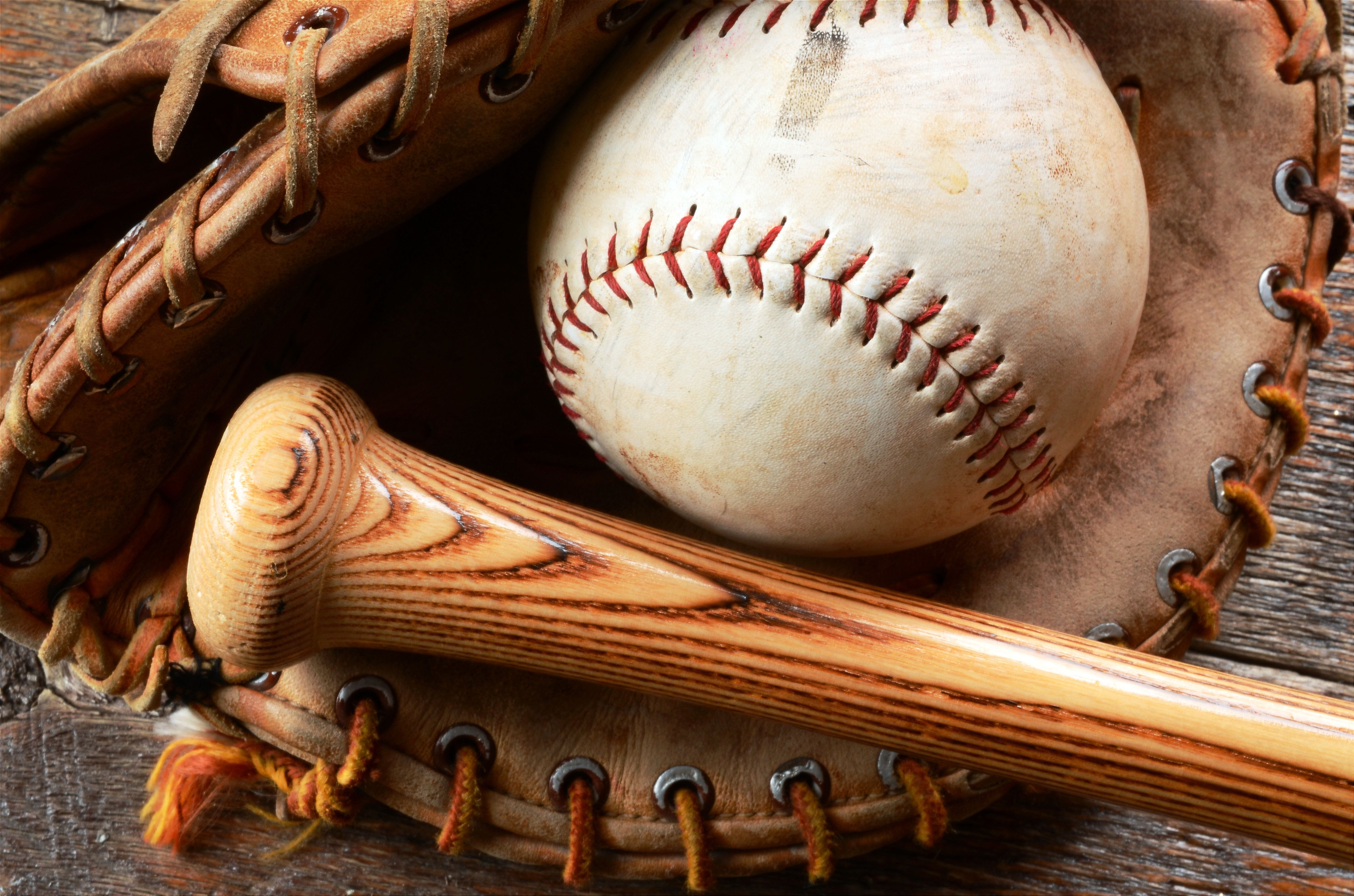 A top view image of old used baseball, baseball glove, and baseball bat.